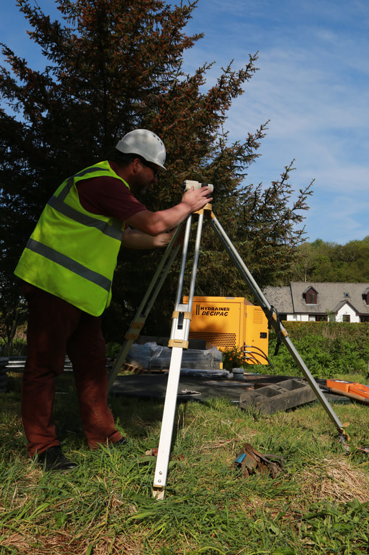 a man operating a dumpy level on a tripod with a house and a tree in the back ground