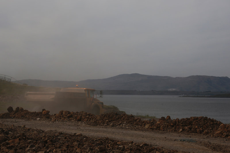 An articulated dump truck driving on site with the hills and the sea in the background and a grey sky
