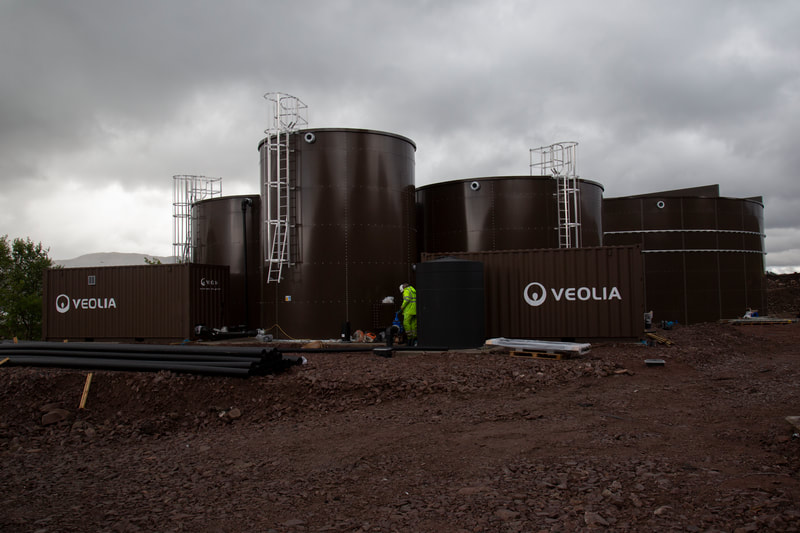 Brown water storage tanks with grey skies in the background