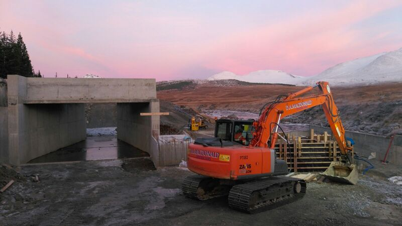 An orange 13 ton excavator working beside a new water intake, with snow capped hills and a moody red sky in the background