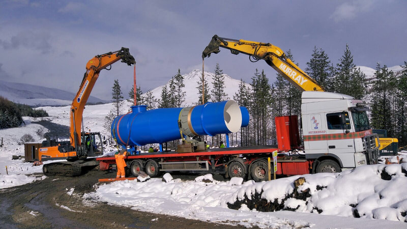 large section of pipe being offloaded from a lorry with 2 excavators