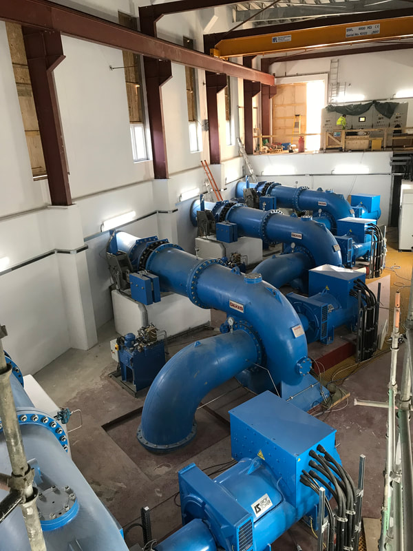 blue Turbines in the lower level inside a large powerhouse