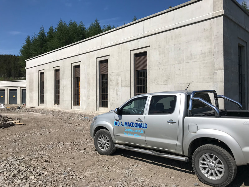 A concrete power station building with tall brown windows, and a silver 4x4 in the foreground