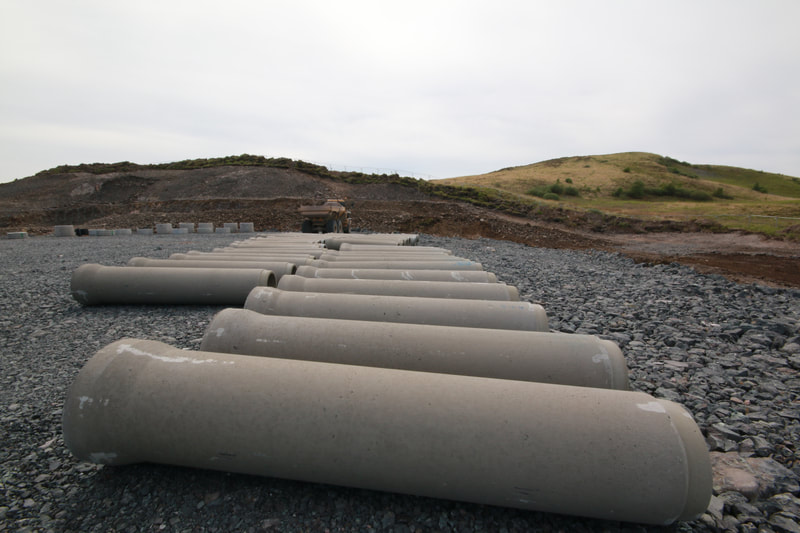 2 rows of concrete pipes lying on crushed rock