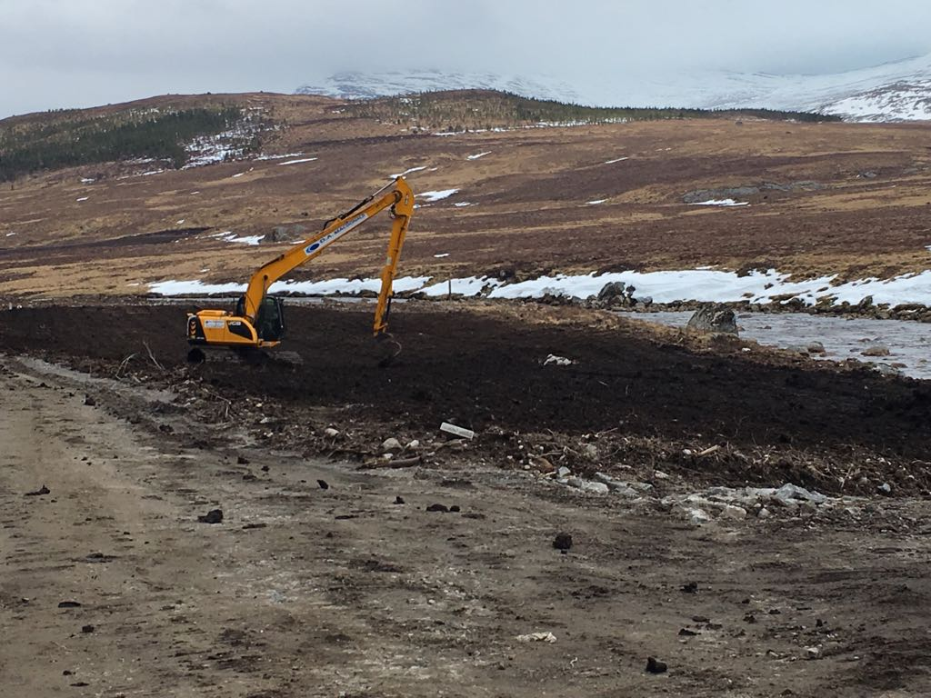 A Yellow long reach excavator spreading soil next to the river, snow capped hills in the background